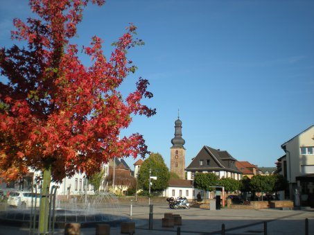 Church, fountain and autumn tree